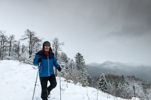 Man trekking in the snow with poles
