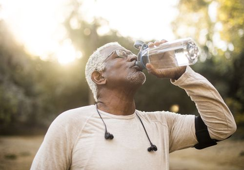 A senior African American Man enjoying refreshing water after a workout