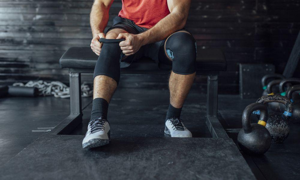 Man putting on knee sleeve