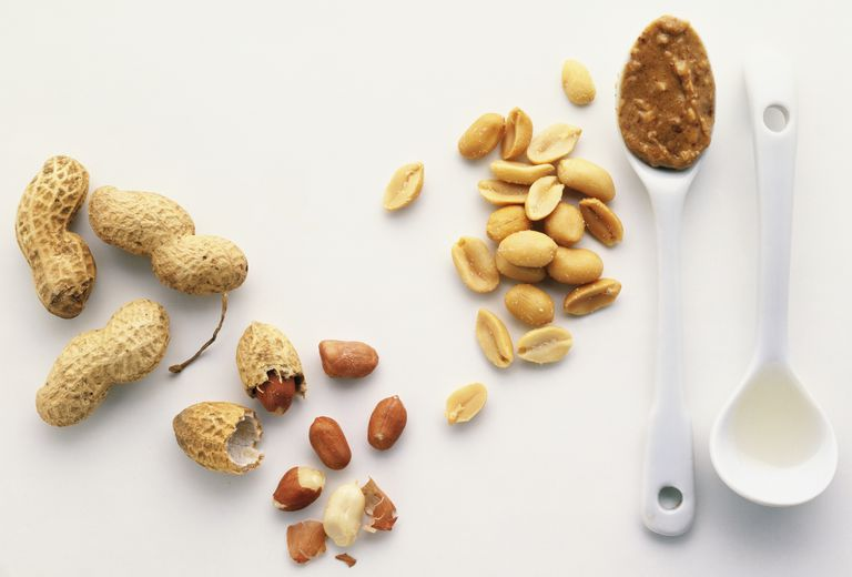 Above view of scattered peanuts, three shelled, one cracked, with skins, two spoons one with crunchy Peanut butter, the other with groundnut oil.