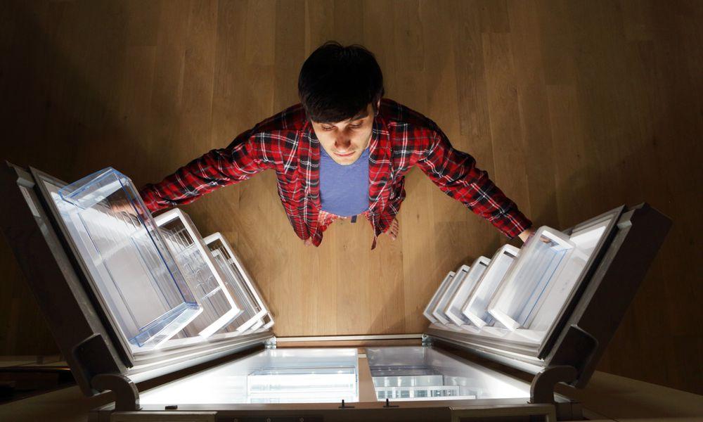 Man looking into empty fridge at night