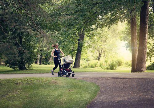 Nueva madre trotar con cochecito en parque público.