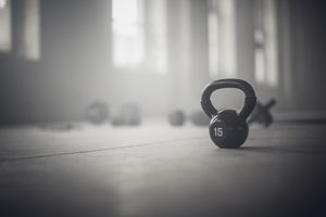 Close up of kettlebell weights on floor of dark gym