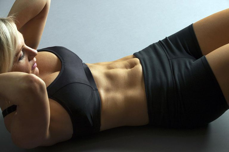 Studio down-shot partial body of fit blonde woman doing sit-up exercise.