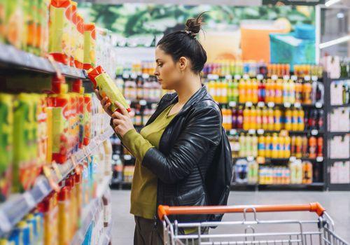 Mujer leyendo la etiqueta de información nutricional para la grasa total