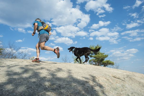 man running with dog and backpack