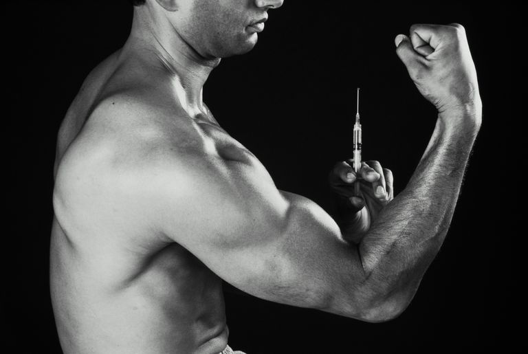 Man about to inject himself with steroids, profile (B&W)
