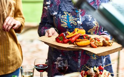 person holding a tray of grilled peppers