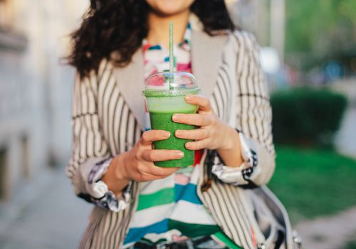 Woman holding green drink