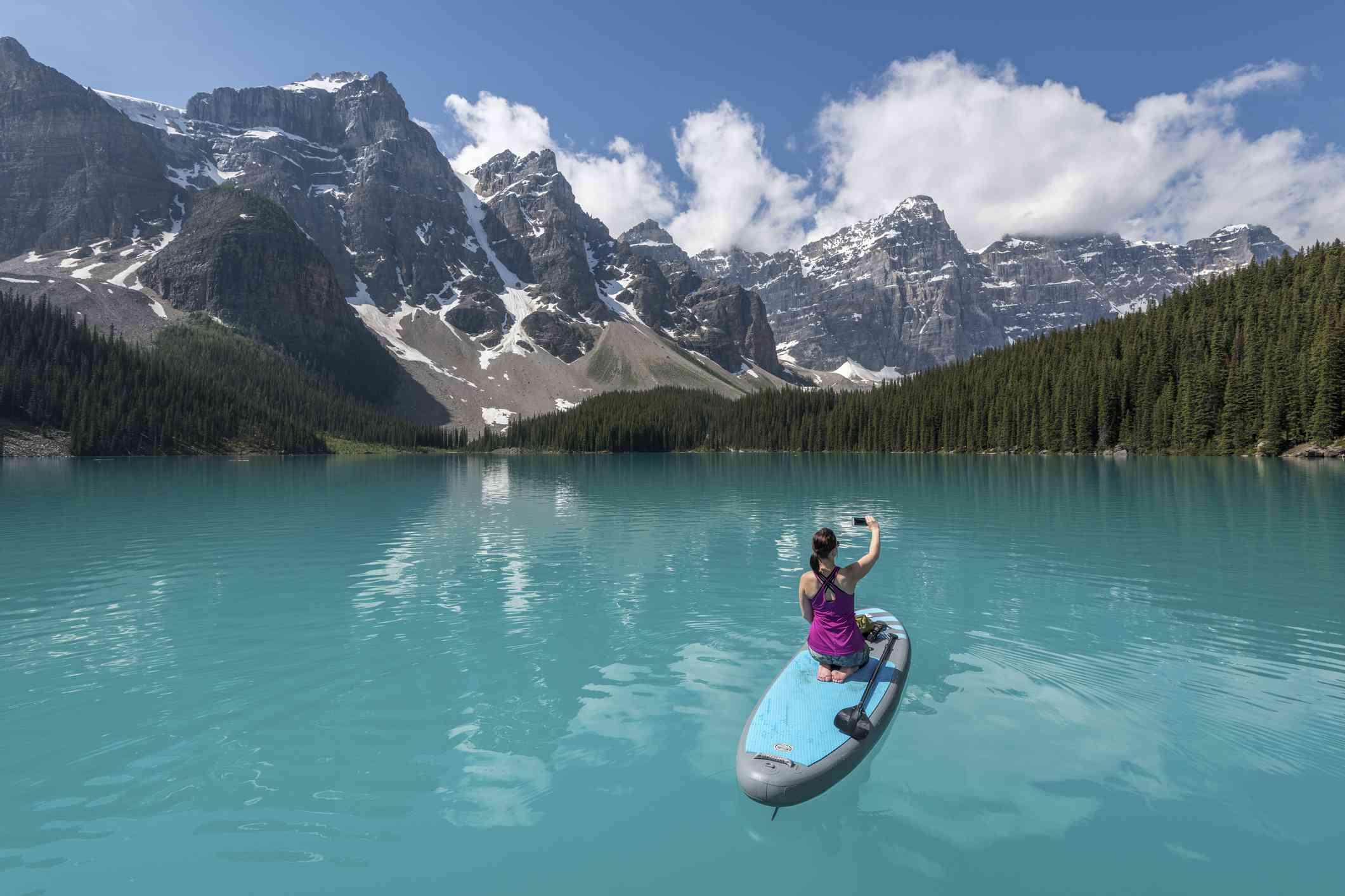 Mujer remando y tomando una foto en el lago Louise
