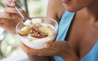 woman eating yogurt with fruit