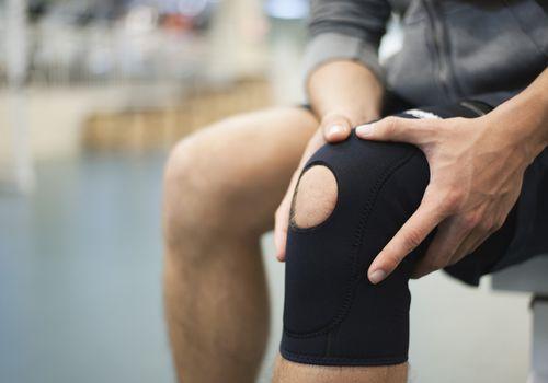 hombre tocando la rodilla lesionada en el aparato ortopédico
