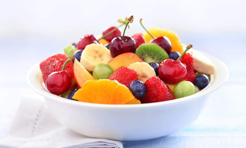 A white bowl of fruit containing sliced oranges, cherries, kiwi, strawberries, grapes, and bananas.