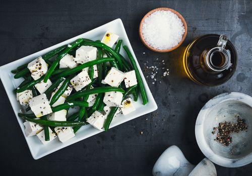 Ensalada de judías verdes y queso feta sobre fondo gris visto desde arriba