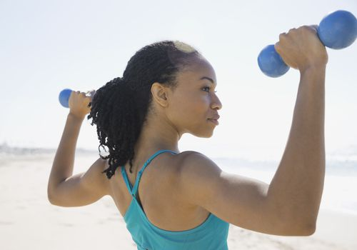 Woman Lifting Weights on the Beach