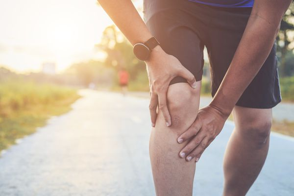 man holding knee while jogging in park