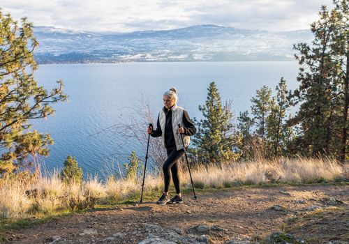 older woman walking on mountain trail with hiking poles for stability