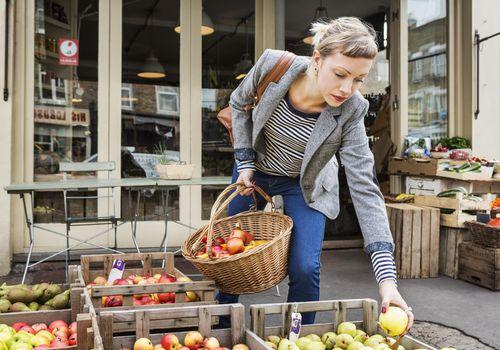 Mujer elegir manzanas en un mercado de agricultores