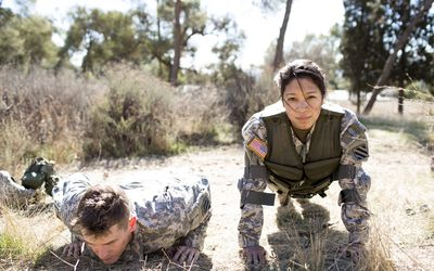 Army woman and man doing pushups in field
