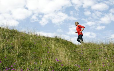 Man running up grassy hillside