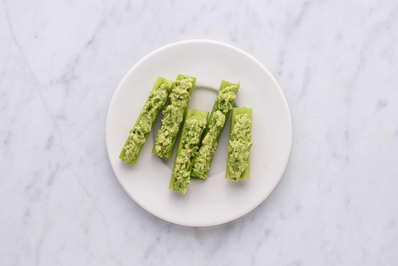 guacamole and celery sticks on a plate