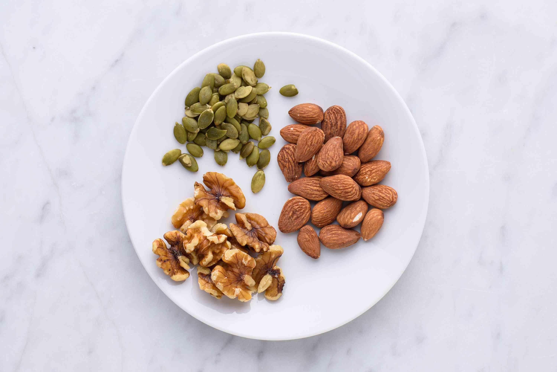 nueces y semillas en un plato, incluyendo semillas de calabaza, almendras y nueces