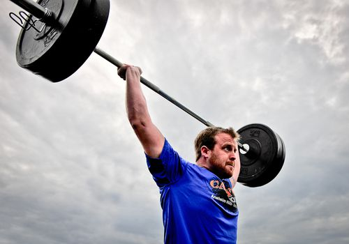 A man completes a push jerk overhead under grey skies.