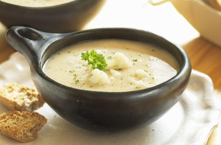 cauliflower cheese soup in a black bowl