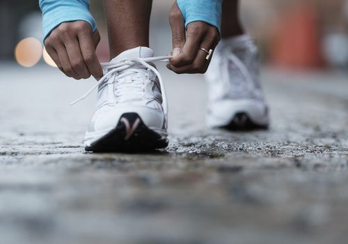 woman's hands tying shoelaces on running shoes