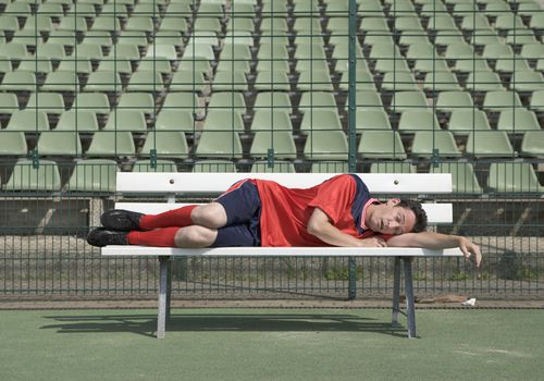 Soccer Player Sleeping in Empty Stadium