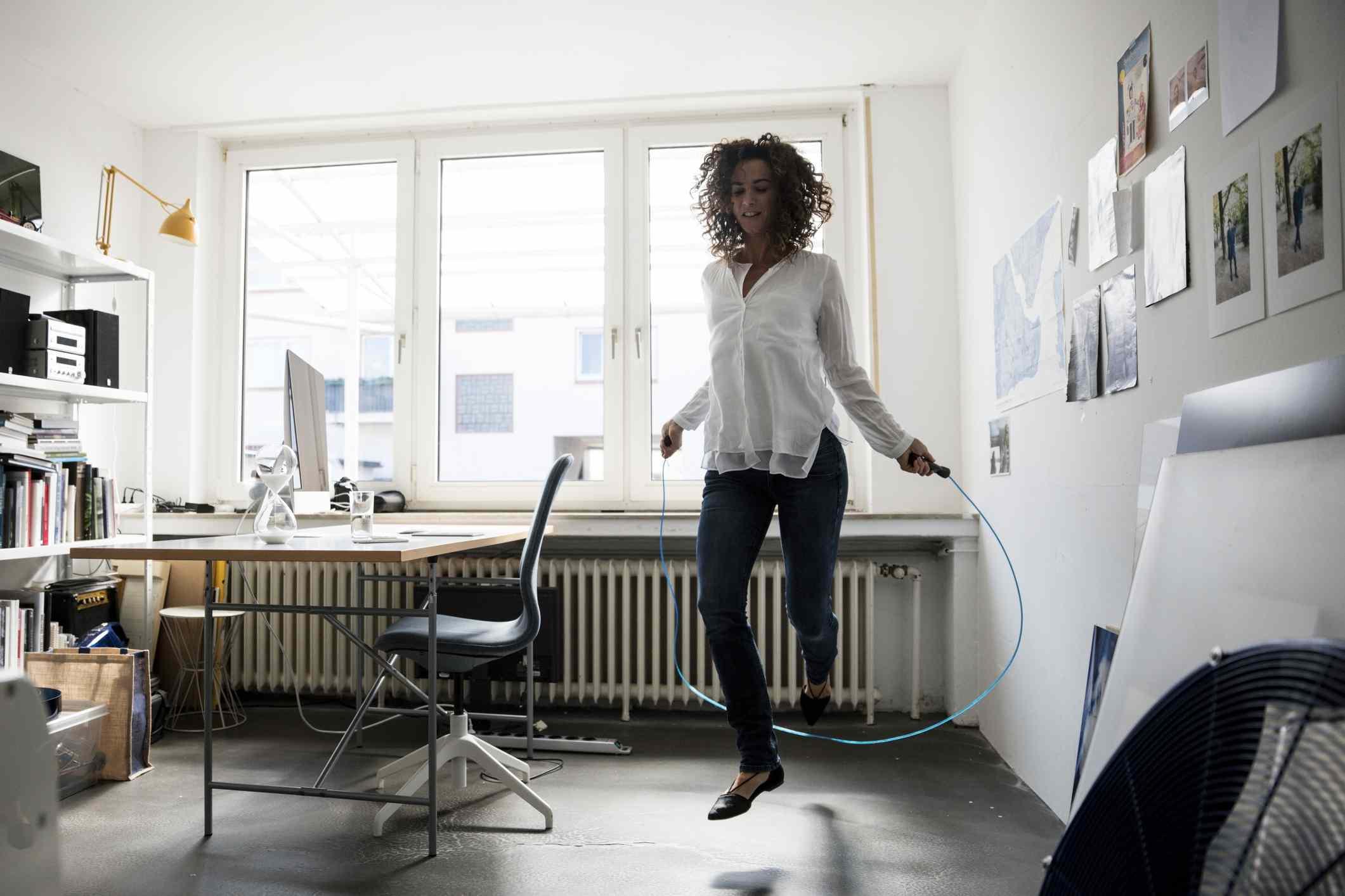 La empresaria en la formación de oficina con saltar la cuerda