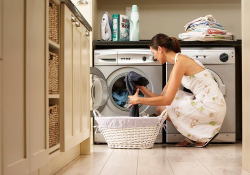 Woman throwing clothes in washing machine