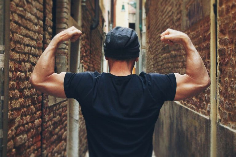 Rear view of man flexing muscles against brick wall