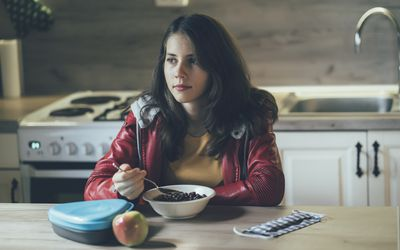 High school student having breakfast in the morning at home before going to school