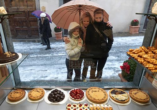 woman and girls looking through bakery window