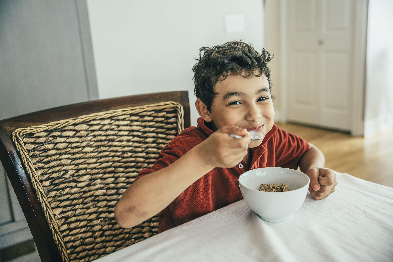 niño comiendo cereal en la mesa