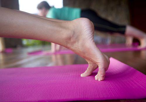 Pies de mujer haciendo una tabla sobre una estera de yoga