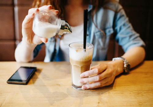 Woman pouring sugar into iced coffee