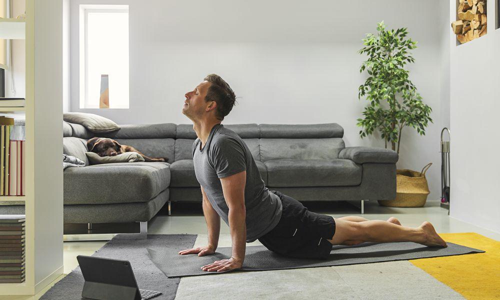 Man doing yoga in living room