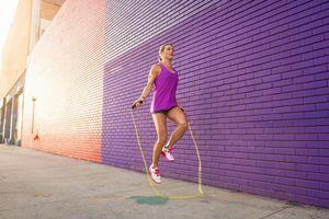 Female runner jumping rope on the sidewalk