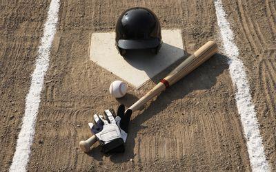 Baseball, bat, batting gloves and baseball helmet at home plate