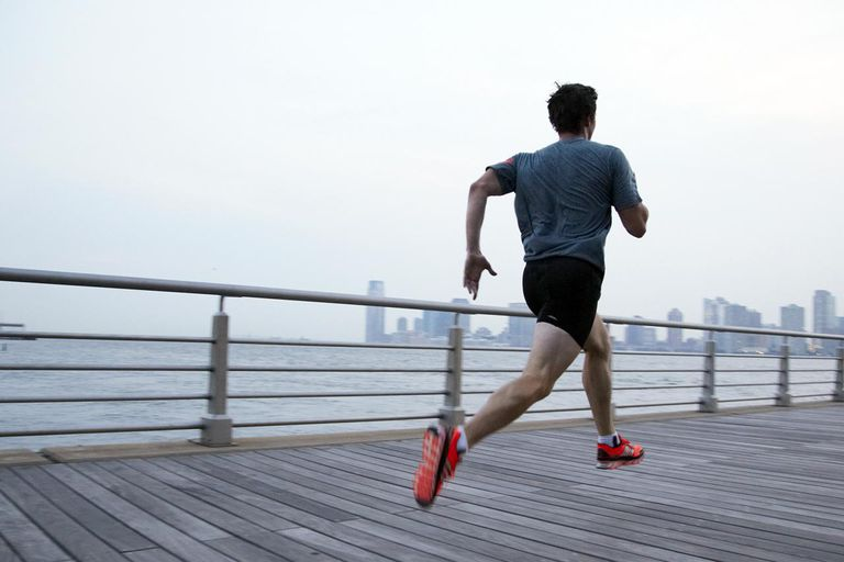 Man running on pier in front of city skyline