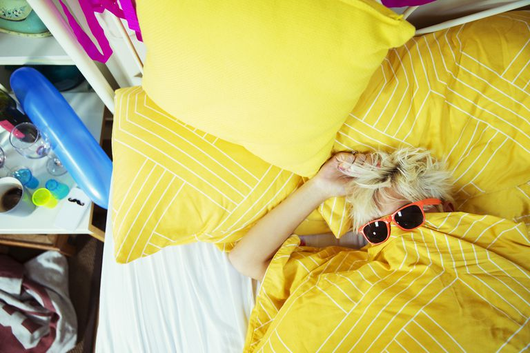 Woman hungover wearing sunglasses in bed