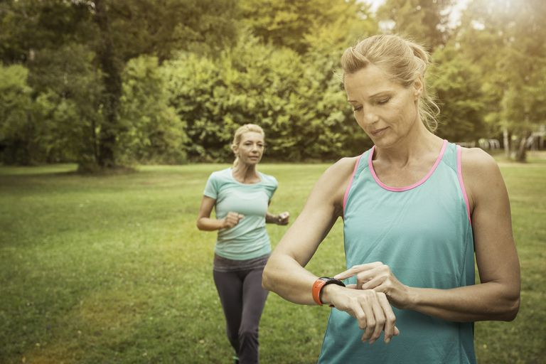 Mature women jogging in park, checking heart rate monitor wrist watch