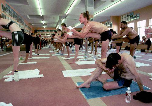 El estudiante de yoga Tom Grant (de Los Ángeles) se sienta en el suelo y toma un descanso durante la clase de yoga de Bikram Choudhury en una sala climatizada, Beverly Hills, California, el 2 de febrero de 2000.