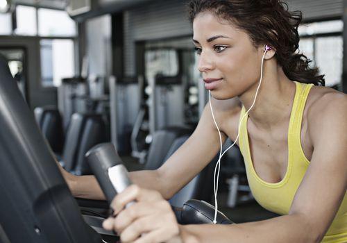 Mujer haciendo ejercicio en la máquina elíptica en el gimnasio