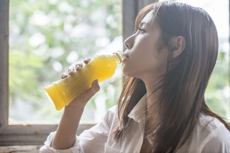 Woman drinking a bottle of Japanese tea.