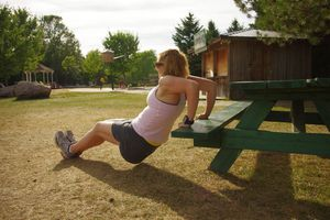 A woman doing tricep dips on a picnic table bench