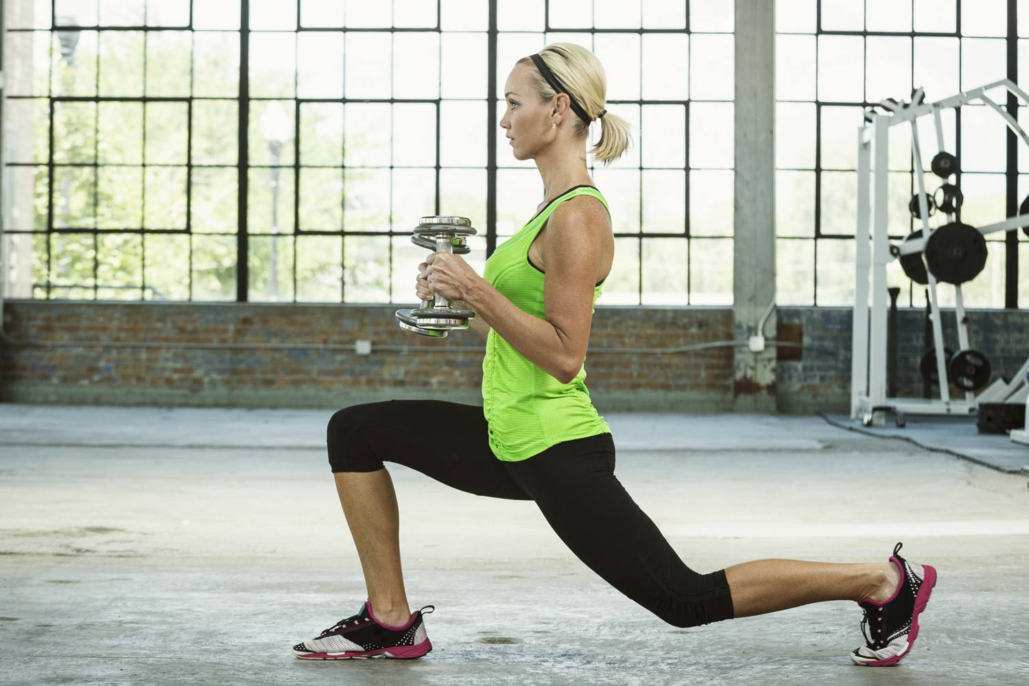 woman doing lunges with dumbells in gym