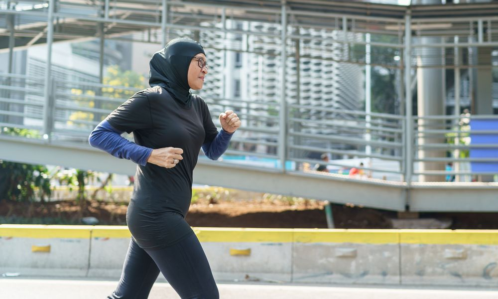 independent woman runner with hijab running on the big city